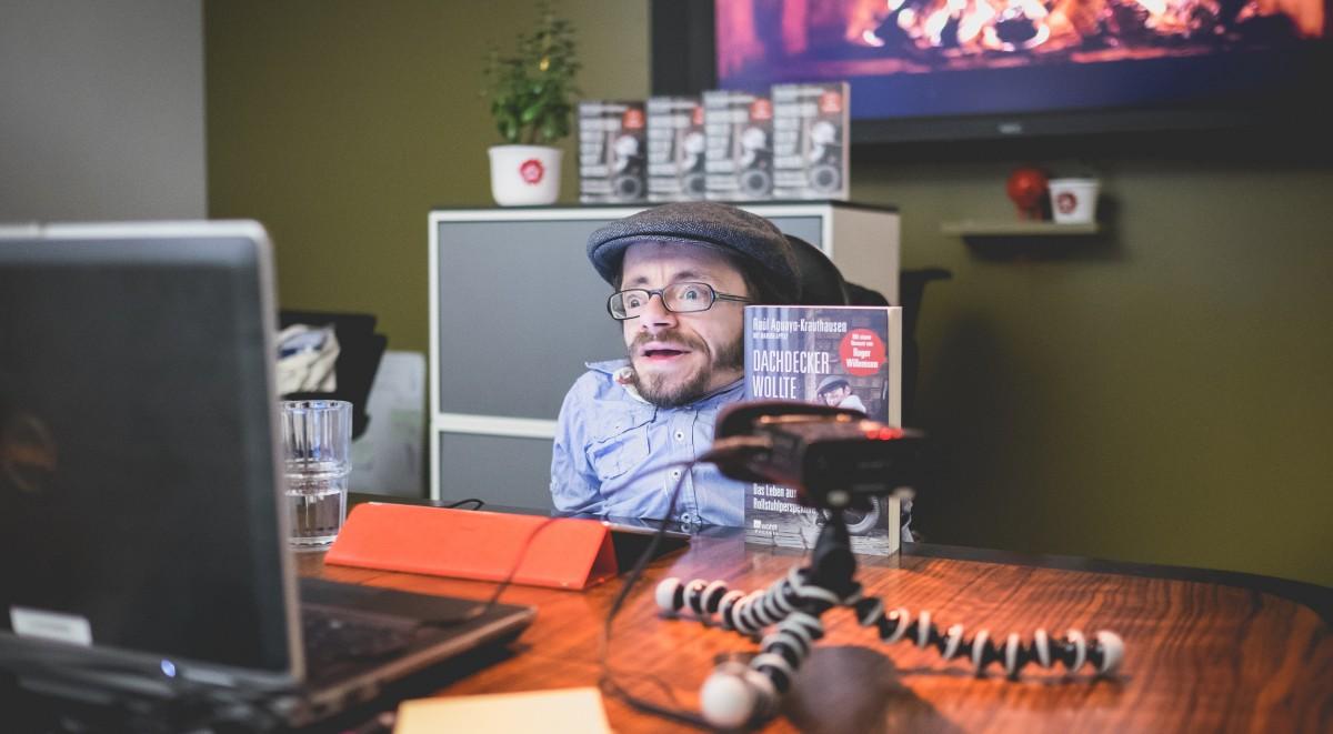 Raul Krauthausen während der Onlinelesung hinter einem Laptop und Aufnahmegerät