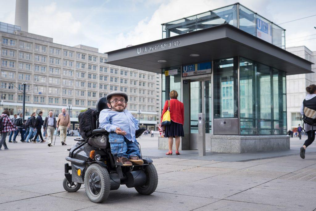 Rollstuhlfahrer Raul Krauthausen steht vor einem aufzug auf dem alexanderplatz in Berlin und guckt in die Kamera