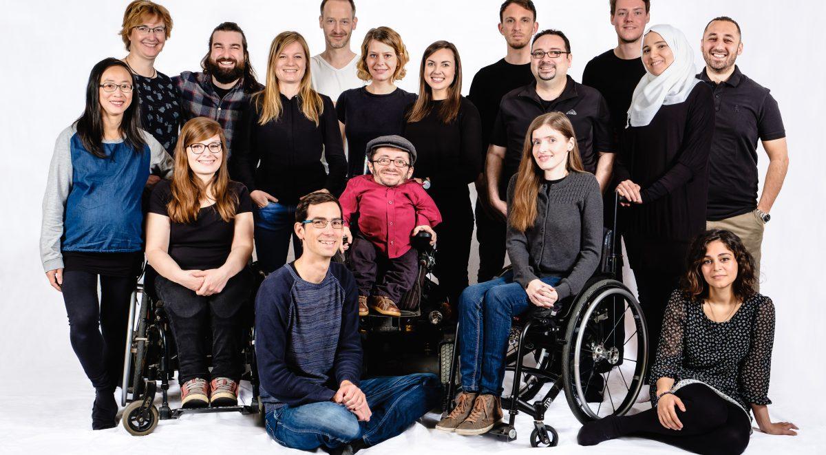 Ein Gruppenbild mit 17 Personen, die in die Kamera lächeln. Von links nach rechts: Hoa, Silke, Judyta, Andi, Lili, Holger, Jonas, Svenja, Raul, Holger, Timo, Adina, Alexander, Hend, Bashar und Sanaz.