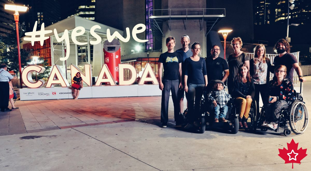 """Das Sozialhelden-Team steht vor einem Canadaschild und darüber steht """"yes we"""""""