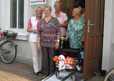 Eine Gruppe von Frauen posieren um eine Rampe herum, eine Frau nutzt diese Rampe mit ihrem Rollator, der gefüllt mit Einkäufen ist