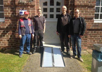 Vier Männer posieren um eine Rampe herum und schauen freundlich.