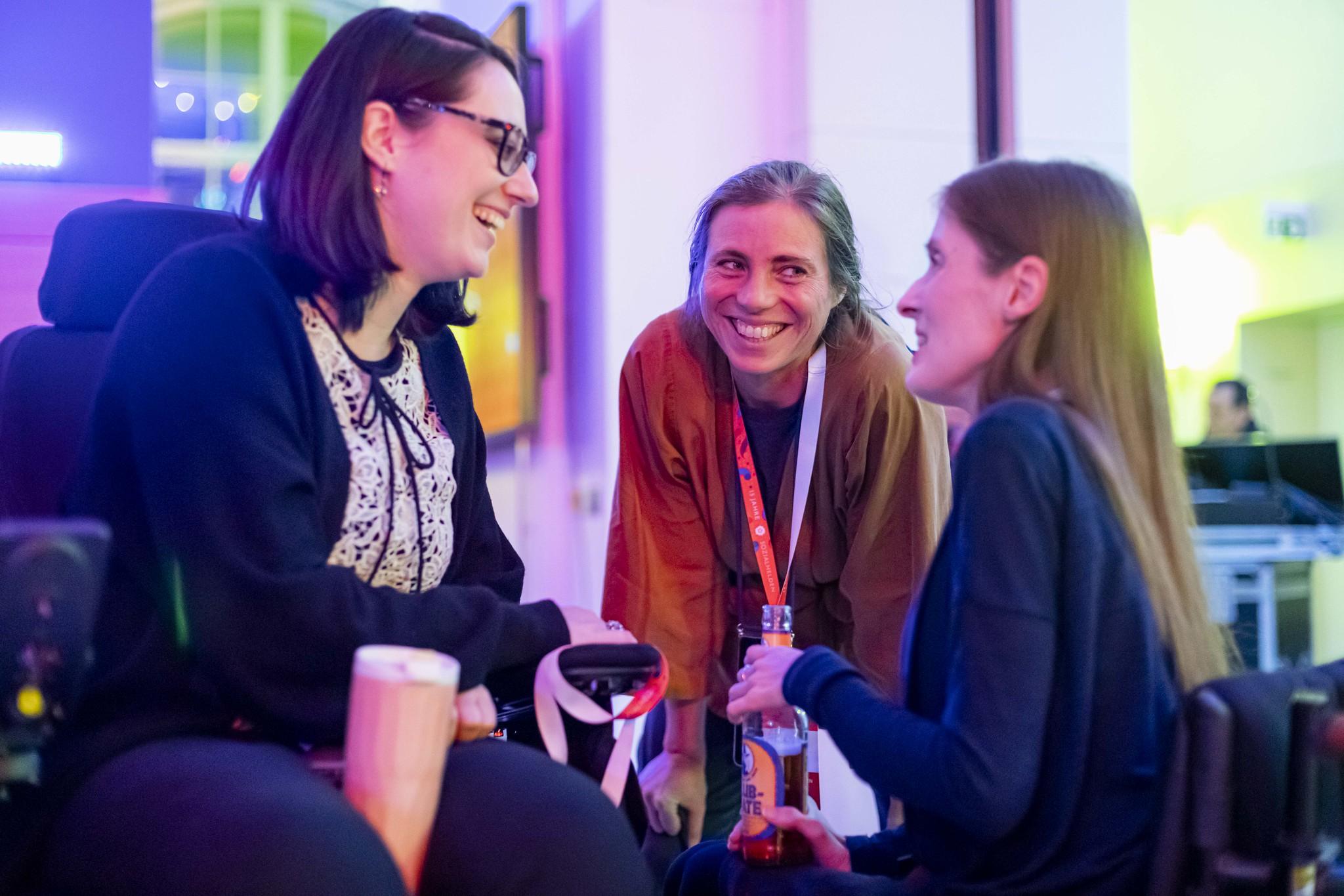 Foto von drei sich unterhaltenden Frauen, zwei im Rollstuhl, alle lächeln