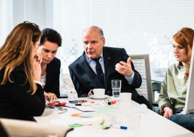 Workshopszenario: Personen sitzen an einem Tisch und diskutieren.