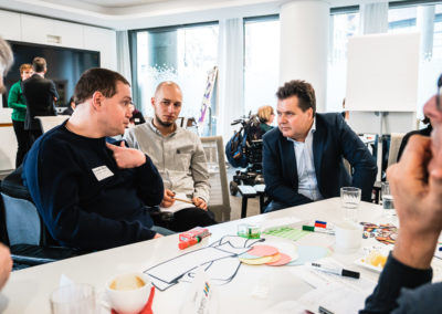 Workshopszenario: An einem Tisch sitzen Männer, die miteinander reden.