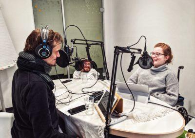 Bild der Aufnahme vom Podcast die Neue Norm, auf dem Bild befinden sich die drei Protagonist:innen an einem Tisch, die Stimmung ist fröhlich.