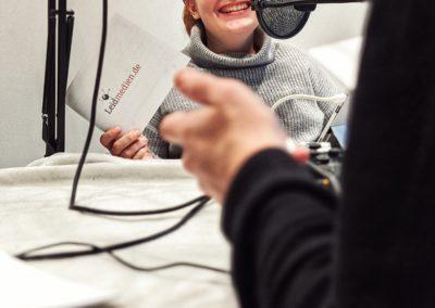 Bild der Aufnahme vom Podcast die Neue Norm, zu sehen ist Judyta Smykowski, die herzlich lacht.
