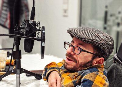 Bild der Aufnahme vom Podcast die Neue Norm, zu sehen ist Raul Krauthausen, der in ein Mikrofon spricht.