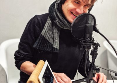 Bild der Aufnahme vom Podcast die Neue Norm, zu sehen ist Jonas Karpa, der in ein Mikrofon spricht.