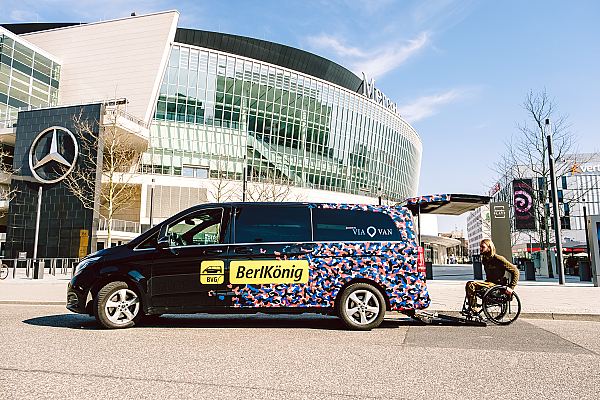 Foto vom Berlkönig Auto vor der Mercedes Benz Arena. Der Kofferraum ist offen und über eine Rampe fährt ein Rollstuhlfahrer hinein.