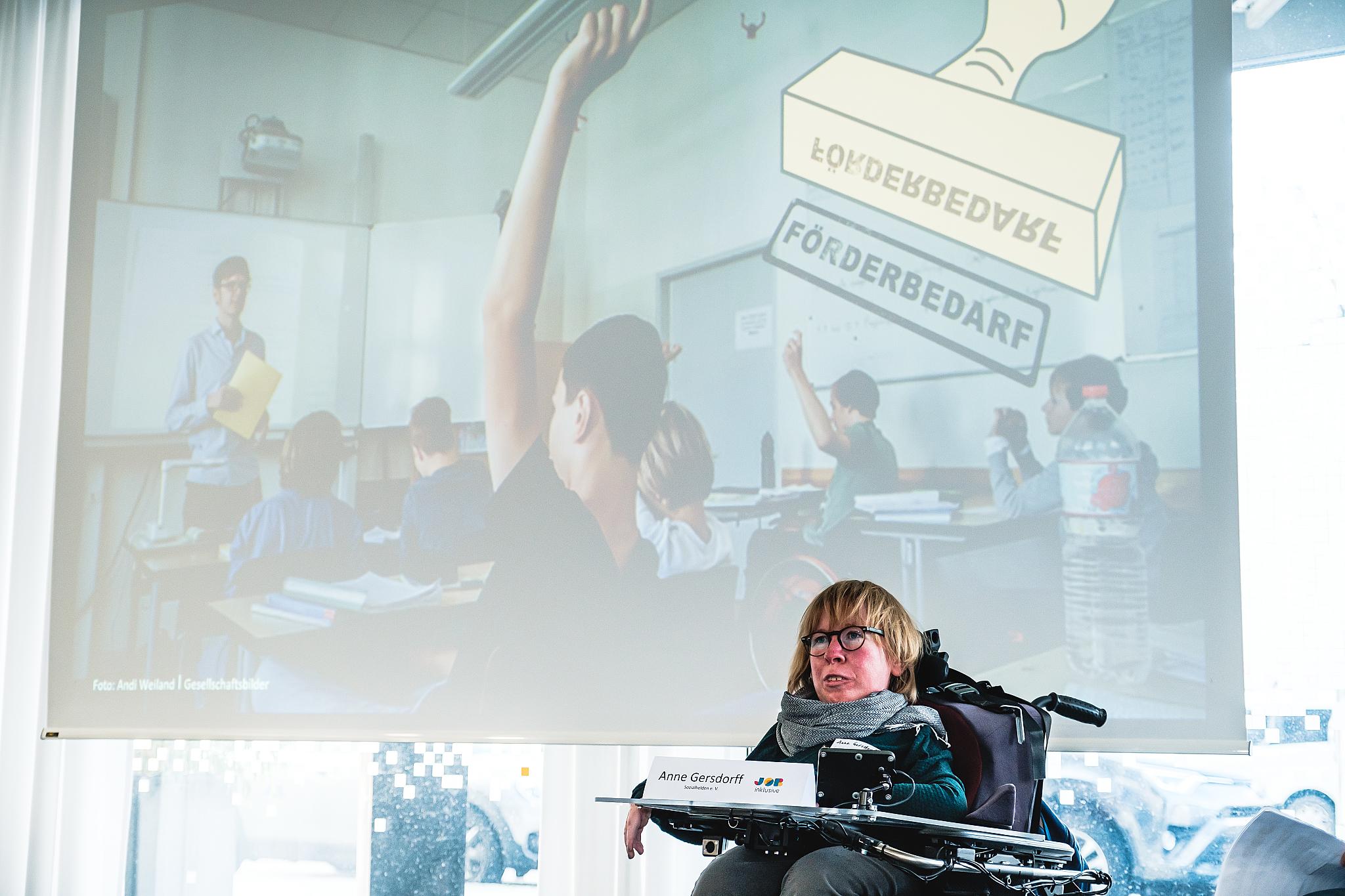 Sozialheldin Anne Gersdorff hält Vortrag. Im Hintergrund ein Beamer mit einem Foto einer Schulklasse.