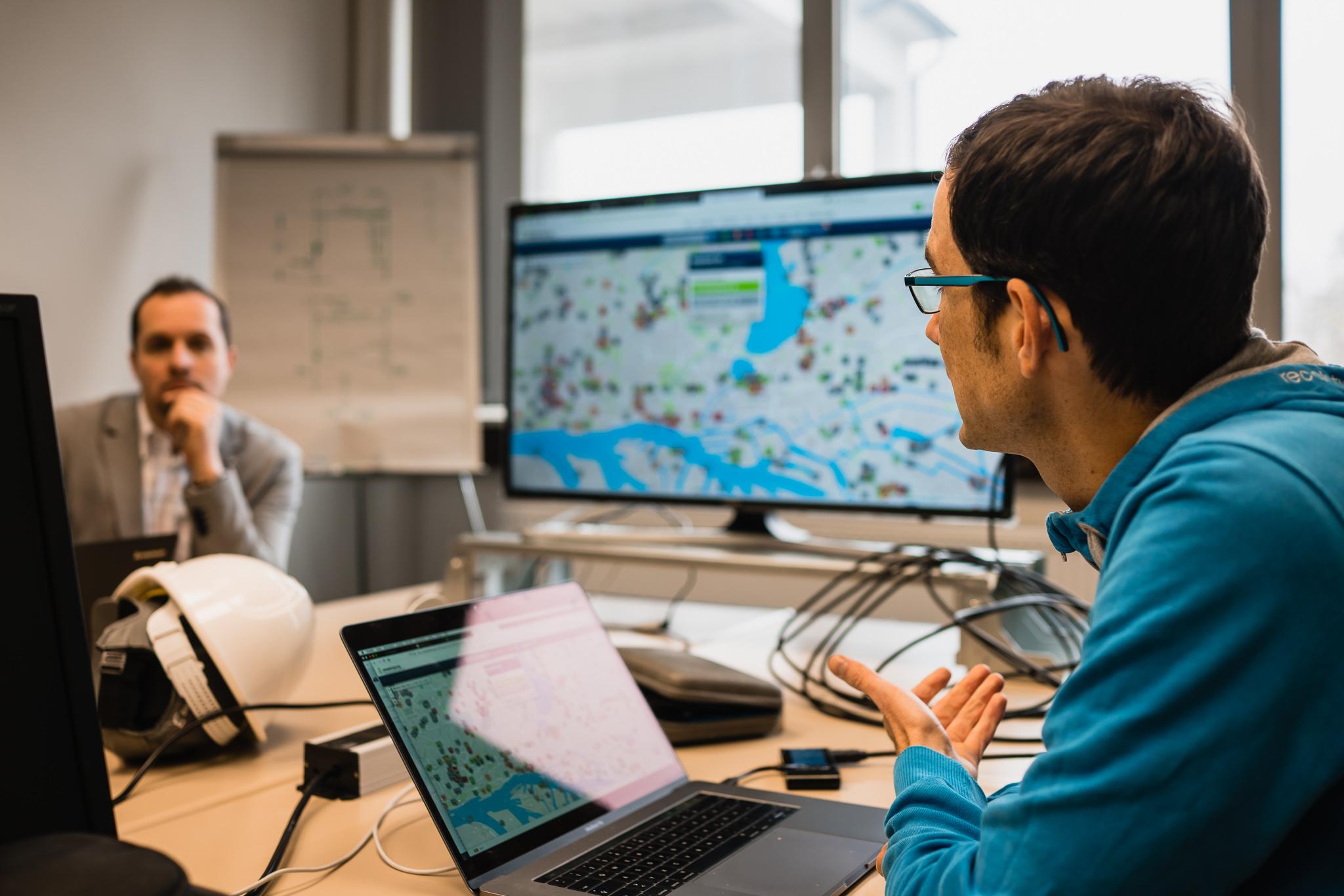 Ein Mann sitzt vor einem Laptop und spricht mit jemanden. Im Hintergrund Bildschirm mit Wheelmap Karte