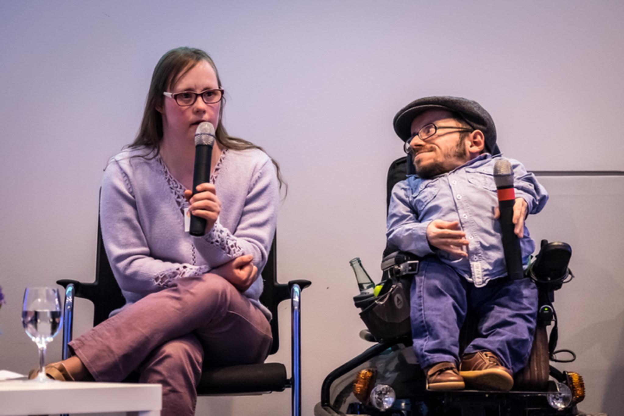Foto Podiumsdiskussion. Links Schauspielerin Carina Kühne mit Mikrofon sprechend, rechts Aktivist Raul Krauthausen mit Mikrofon.