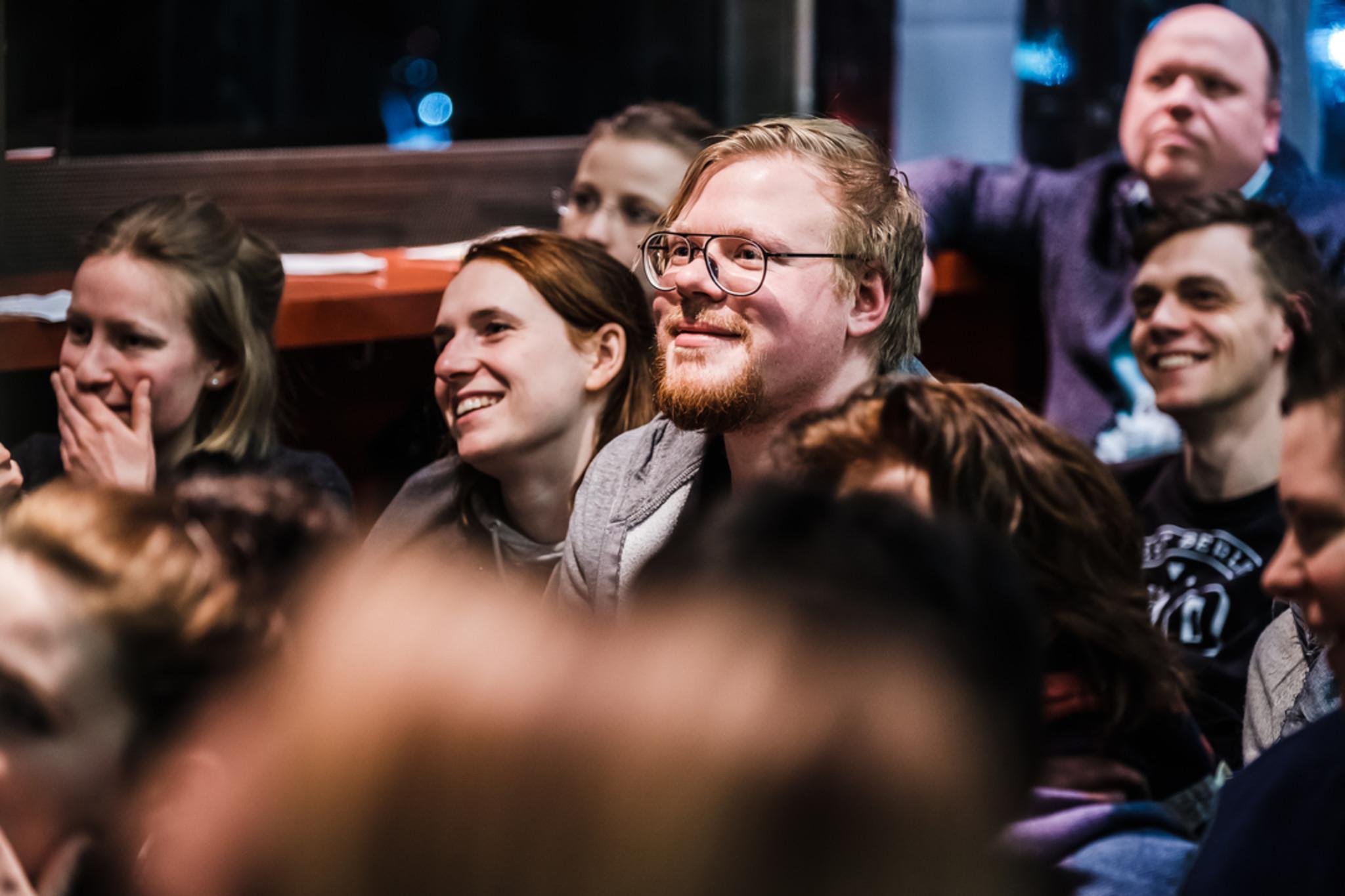 Blick in Zuschauerraum einer Veranstaltung der Sozialhelden. Personen lächeln und lachen.