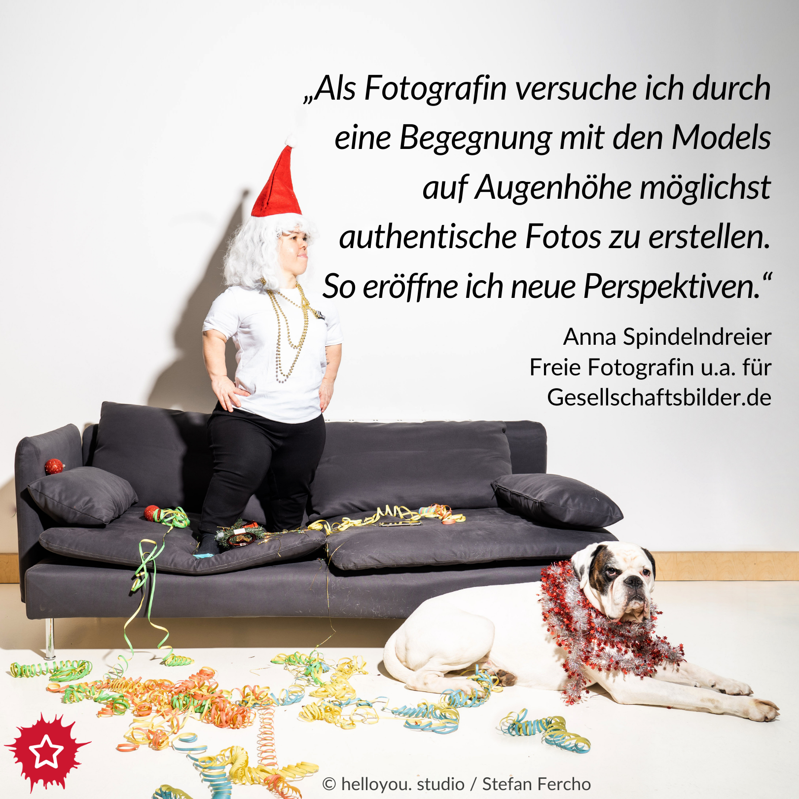 """Foto von Anna Spindelndreier. Sie steht auf einem grauen Sofa und trägt eine rote Weihnachtsmütze. Vor dem Sofa sitzt ein großer weißer Hund. Überall liegen Luftschlangen. Daneben der Text """"Als Fotografin versuche ich durch eine Begegnung mit den Models auf Augenhöhe möglichst authentische Fotos zu erstellen. So eröffne ich neue Perspektiven."""""""