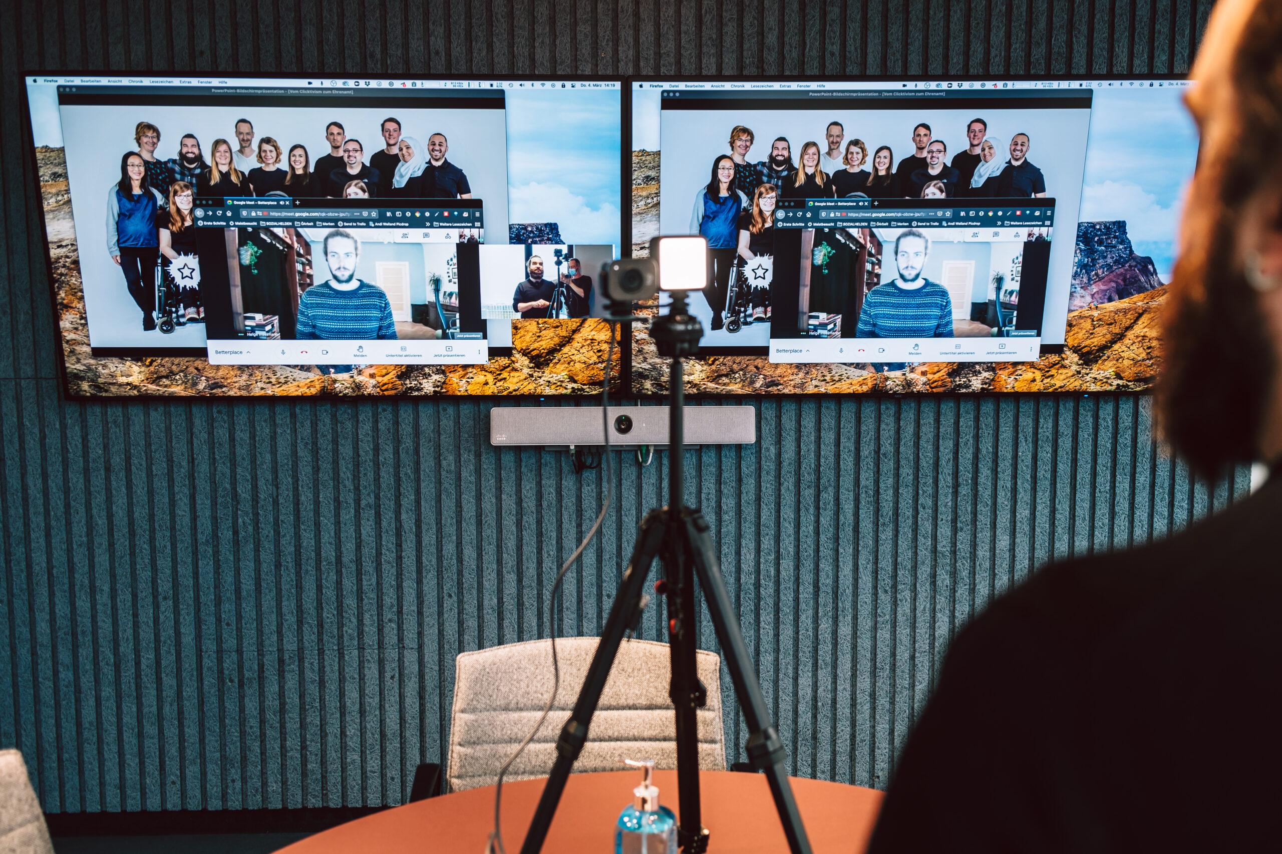 Zwei Bildschirme mit dem Team der Sozialhelden drauf. Um Vordergrund spricht ein bärtiger Mann zu einer Webcam hin